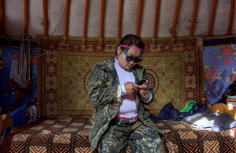 This picture taken on June 27, 2016 shows national park ranger Surenjav Munkhsaikhan trying to get signal for her mobile phone in a yurt near the Flaming Cliffs in the Gobi desert. For years, herder Gelegrash had a sideline bringing tourists to see a dinosaur skull hidden near the Flaming Cliffs in Mongolia's Gobi desert. Then, one day, it was gone. It is one of thousands of ancient fossils that have disappeared from the country since American explorer Roy Chapman Andrews -- supposedly the inspiration for the movie character Indiana Jones -- discovered dinosaur eggs there nearly a century ago. (JOHANNES EISELE/AFP/Getty Images)
