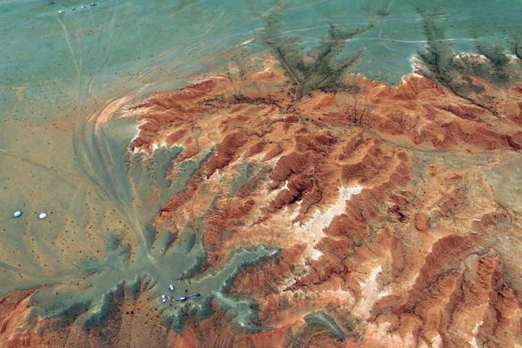 This aerial picture taken on June 27, 2016 shows the Flaming Cliffs in the Gobi desert. For years, herder Gelegrash had a sideline bringing tourists to see a dinosaur skull hidden near the Flaming Cliffs in Mongolia's Gobi desert. Then, one day, it was gone. It is one of thousands of ancient fossils that have disappeared from the country since American explorer Roy Chapman Andrews -- supposedly the inspiration for the movie character Indiana Jones -- discovered dinosaur eggs there nearly a century ago. (JOHANNES EISELE/AFP/Getty Images)