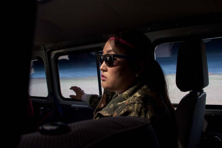 This picture taken on June 27, 2016 shows national park ranger Surenjav Munkhsaikhan sitting in a car near the Flaming Cliffs in the Gobi desert. For years, herder Gelegrash had a sideline bringing tourists to see a dinosaur skull hidden near the Flaming Cliffs in Mongolia's Gobi desert. Then, one day, it was gone. It is one of thousands of ancient fossils that have disappeared from the country since American explorer Roy Chapman Andrews -- supposedly the inspiration for the movie character Indiana Jones -- discovered dinosaur eggs there nearly a century ago. (JOHANNES EISELE/AFP/Getty Images)