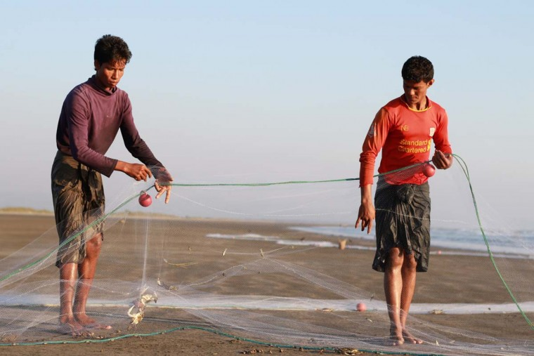 In this photograph taken on December 13, 2016, Muslim fishermen gather their net while they fish on the shore of Maungdaw facing the Bay of Bengal located in Myanmar's strife-torn Rakhine State near the Bangladesh border. Almost 27,000 Rohingya have crossed into Bangladesh since the beginning of November, the UN said on December 13, fleeing a bloody military campaign in Myanmar's western Rakhine state. (KHINE HTOO MRAT/AFP/Getty Images)