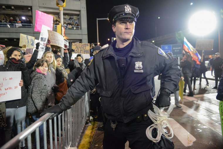 NEW YORK, NY - JANUARY 28: A police officer stands guard as protestors rally during a demonstration against the new immigration ban issued by President Donald Trump at John F. Kennedy International Airport on January 28, 2017 in New York City. President Trump signed the controversial executive order that halted refugees and residents from predominantly Muslim countries from entering the United States. (Photo by Stephanie Keith/Getty Images)