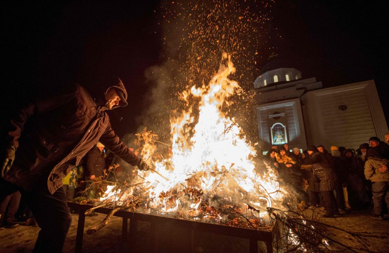 A man burns dried oak branches, the Yule log symbol for the Orthodox Christmas Eve in front of Saint Demetrios church in Belgrade, on January 6, 2017, during the Christmas Orthodox Day. The branches are also carried into the homes and burned on Orthodox Christmas Day, which is celebrated according to the Julian calendar, January 7, 2016. (AFP PHOTO / OLIVER BUNIC)