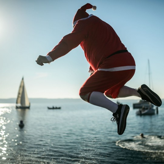 A man wearing a Santa Claus suit jumps into the water during a traditional New Year's swim in the Adriatic sea in Portoroz, Slovenia, on January 1, 2017. (AFP PHOTO / Jure MAKOVEC)