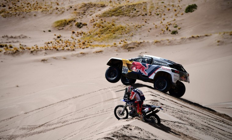 Peugeot's French driver Sebastien Loeb and co-driver Daniel Elena of Monaco (back) and Yamaha's Japanese biker Shinnosuke Kazama compete during Stage 4 of the 2017 Dakar Rally between San Salvador de Jujuy in Argentina and Tupiza in Bolivia, on January 5, 2017. (Franck Fife/AFP/Getty Images)
