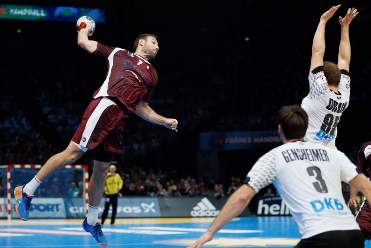Qatar's left back Bertrand Roine (left) jumps to shoot on goal during the 25th IHF Men's World Championship 2017 eighth final handball match Germany vs Qatar on January 22, 2017 at the AccorHotels Arena in Paris. (THOMAS SAMSON/AFP/Getty Images)