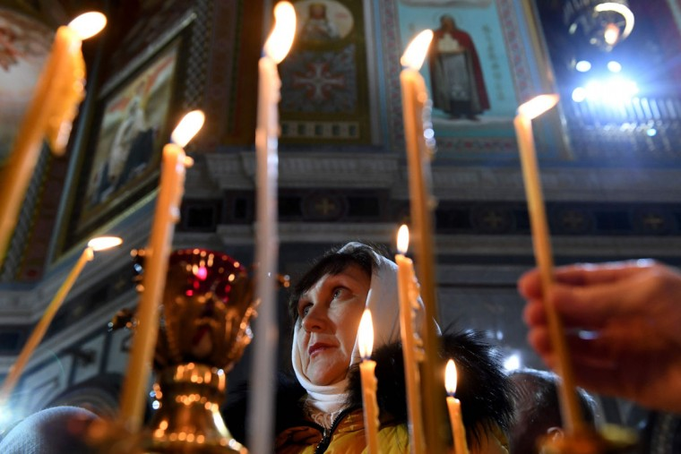 A Russian Orthodox believer attends a Christmas service in Christ the Savior cathedral in Moscow early on January 7, 2017. Orthodox Christians celebrate Christmas on January 7 in the Middle East, Russia and other Orthodox churches that use the old Julian calendar instead of the 17th-century Gregorian calendar adopted by Catholics, Protestants, Greek Orthodox and commonly used in secular life around the world. (AFP PHOTO / Kirill KUDRYAVTSEV)