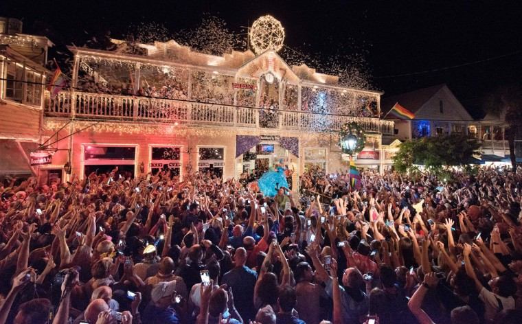 "Duval Street in Key West, Florida is jammed with revelers outside the Bourbon St. Pub early Sunday, January 1, 2017. Thousands watched female impersonator, Gary Marion (C) as ""Sushi,"" descend in an oversized women's red high-heel shoe. The Red Shoe Drop is a Key West New Year's Eve tradition and is one of four Florida Keys warm-weather takeoffs on New York City's Times Square ball drop marking the arrival of the new year. (AFP PHOTO / Florida Keys News Bureau / Rob O'Neal)"