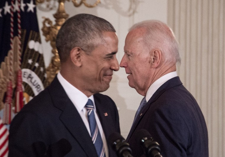 U.S. Vice President Joe Biden and President Barack Obama walk past each other during a tribute to Biden at the White House in Washington, DC, on January 12, 2017. (Nicholas Kamm/AFP/Getty Images)
