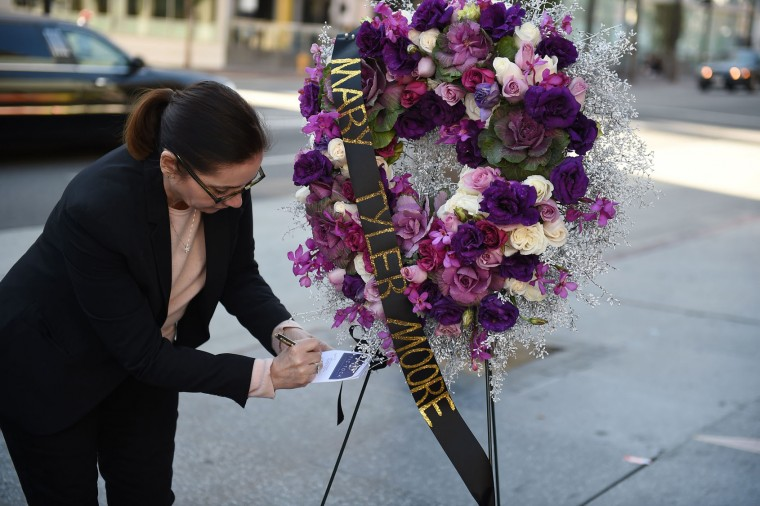 Ana Martinez of the Hollywood Chamber of Commerce signs a card on a wreath for actress Mary Tyler Moore beside her star on the Hollywood Walk of Fame on January 25, 2017 in Hollywood, California. Legendary actress Mary Tyler Moore, who delighted a generation of Americans with her energetic comic performances and broke barriers with her iconic portrayal of a single career woman, died on January 25, 2017 after years of ill health. She was 80. (Robyn Beck/AFP/Getty Images)