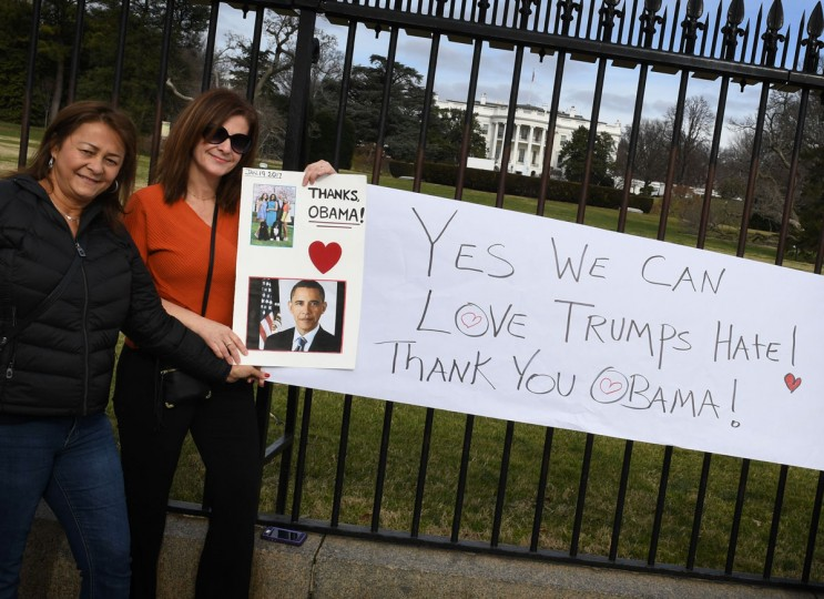 Supporters of US President Barack Obama hold thank you message to the outgoing President outside the White House in Washington, DC, on January 19, 2017, as final preparations are underway a day ahead of the inauguration of the 45th US president. (AFP PHOTO / Mark RALSTON)