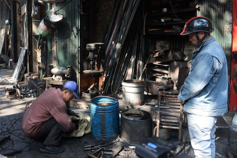 This picture taken on December 8, 2016 shows Nguyen Phuong Hung (L) preparing to hand over ordered items to a customer at his shop on Lo Ren street in downtown Hanoi. Sitting before a bright orange flame, Vietnamese blacksmith Nguyen Phuong Hung prods a fire pit with a long metal rod before he hammers, bends, and contorts glowing steel into a giant drill bit. Hung, who toils away in his tiny corner stall in downtown Hanoi, is the last remaining blacksmith on Hanoi's Lo Ren street, named after the masters of metal it was once known for. (HOANG DINH NAM/AFP/Getty Images)