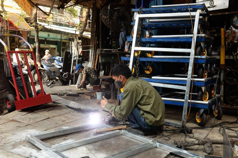 This picture taken on December 8, 2016 shows men working at a metal tools and houseware goods shop on Lo Ren street in downtown Hanoi. Sitting before a bright orange flame, Vietnamese blacksmith Nguyen Phuong Hung prods a fire pit with a long metal rod before he hammers, bends, and contorts glowing steel into a giant drill bit. Hung, who toils away in his tiny corner stall in downtown Hanoi, is the last remaining blacksmith on Hanoi's Lo Ren street, named after the masters of metal it was once known for. (HOANG DINH NAM/AFP/Getty Images)
