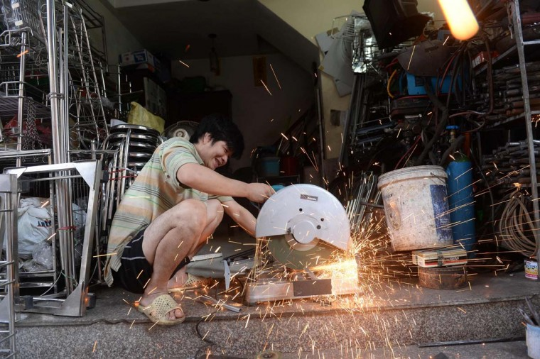This picture taken on December 8, 2016 shows a man working at a metal tools and houseware goods shop on Lo Ren street in downtown Hanoi. Sitting before a bright orange flame, Vietnamese blacksmith Nguyen Phuong Hung prods a fire pit with a long metal rod before he hammers, bends, and contorts glowing steel into a giant drill bit. Hung, who toils away in his tiny corner stall in downtown Hanoi, is the last remaining blacksmith on Hanoi's Lo Ren street, named after the masters of metal it was once known for. (HOANG DINH NAM/AFP/Getty Images)