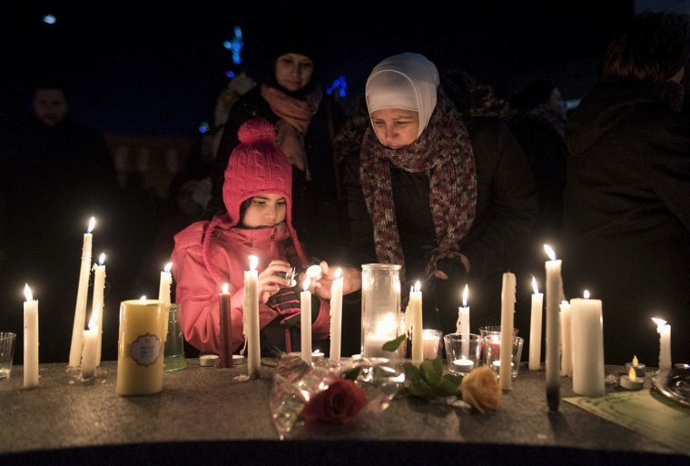 Sawsan Idris, right, lights candles with her daughters Lara and Tamara while attending a vigil in Moncton, New Brunswick, Monday, Jan. 30, 2017, for victims of the shooting at a Quebec City mosque. (Darren Calabrese/The Canadian Press via AP)
