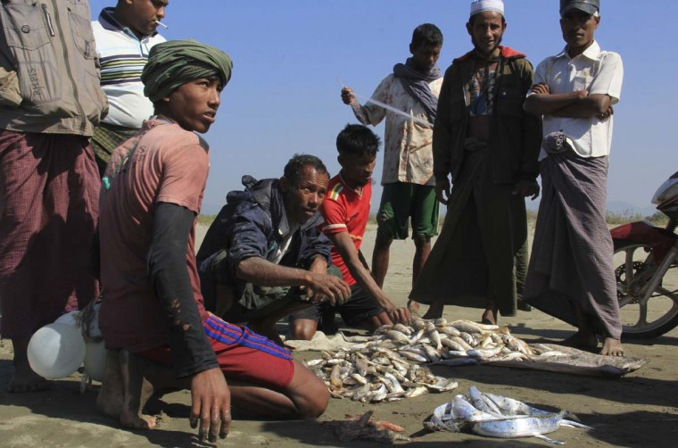 In this Jan. 16, 2017, photo, Rohingya fishermen sell fish caught from makeshift rafts made from recycled plastic containers in Maungdaw, western Rakhine state, Myanmar. Their usual, sturdy fishing boats were outlawed three months ago when Myanmar authorities launched a sweeping and violent counter-insurgency campaign in Rakhine state, home to the long-persecuted Rohingya Muslim minority. The ban on fishing boats -- meant to prevent insurgents from entering or leaving the country by sea -- is just one small provision in the wider crackdown, in which authorities have been accused of widespread abuses. (AP Photo/Esther Htusan)
