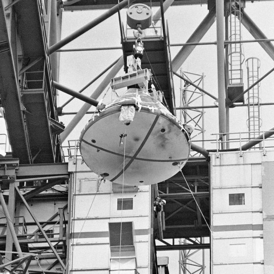 FILE - In this Feb. 17, 1967 file photo, the Apollo 1 capsule, with black smudge marks visible on the heat shield, is lowered from its Saturn 1 booster at Cape Kennedy, Fla. During a launch pad test on Jan. 27, 1967, a flash fire erupted inside the craft killing the three Apollo crew members aboard. (AP Photo/Jim Kerlin, Pool)