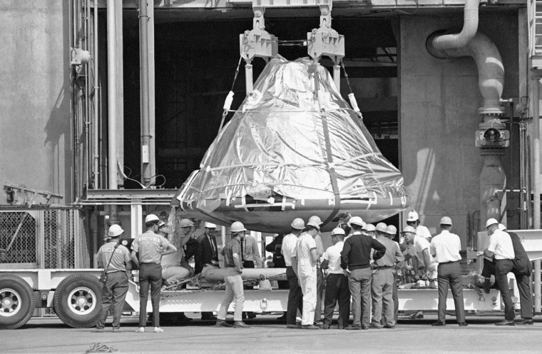 FILE - In this Feb. 17, 1967 file photo, technicians and officials inspect the aluminum covered Apollo 1 spacecraft after it was lowered from its booster at pad 34 at Cape Kennedy, Fla. Astronauts Virgil Grissom, Edward White and Roger Chaffee lost their lives when a flash fire erupted in the spacecraft on January 27. (AP Photo/Jim Kerlin, Pool)