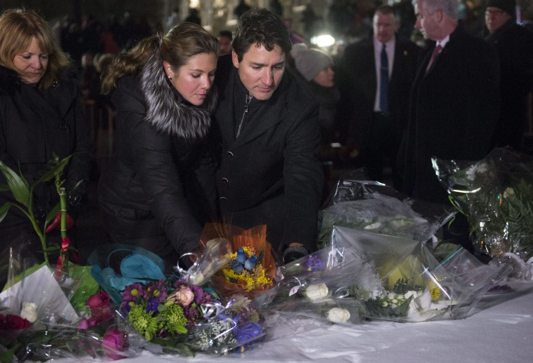 Canadian Prime Minister Justin Trudeau and his wife Sophie Gregoire Trudeau place flowers at a makeshift memorial during a vigil in Quebec City on Monday, Jan. 30, 2017. A gunman shot and killed several people at a Quebec City mosque on Sunday. (Paul Chiasson/The Canadian Press via AP)
