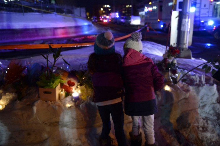 Children look at flowers and candles at a tribute outside a mosque in Quebec City on Monday, Jan. 30, 2017, where a gunman shot and killed several people on Sunday night. (Paul Chiasson/The Canadian Press via AP)