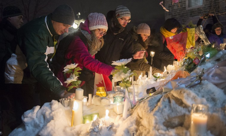 People place candles during a vigil in Quebec City on Monday, Jan. 30, 2017, for victims of Sunday's deadly shooting at a Quebec City mosque. (Paul Chiasson/The Canadian Press via AP)