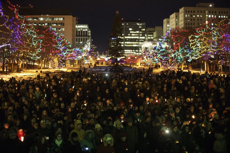 People gather in remembrance of the victims of Sunday's shooting at a Quebec City mosque, during a vigil in Edmonton, Alberta, Monday, Jan. 30, 2017. A French Canadian known for far-right, nationalist views was charged Monday with six counts of first-degree murder and five counts of attempted murder over the shooting rampage at a Quebec City mosque that Canada's prime minister called an act of terrorism against Muslims. (Jason Franson/The Canadian Press via AP)