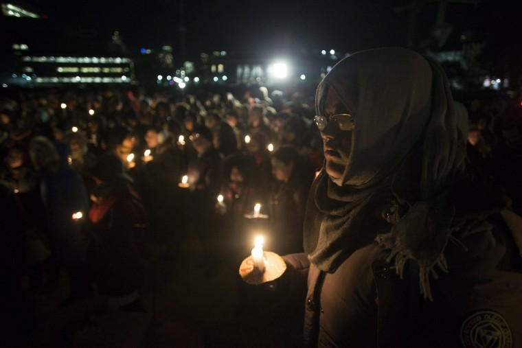 People gather to observe a candlelight vigil in Toronto on Monday, Jan. 30, 2017, for victims of Sunday's deadly shooting at a Quebec City mosque. (Chris Young/The Canadian Press via AP)