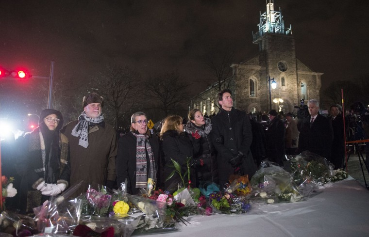 Suzanne Pilote, from left, her husband Quebec Premier Philippe Couillard, Quebec City Mayor Regis Labeaume, his wife Louise Vien, Sophie Gregoire Trudeau and Prime Minister Justin Trudeau pause after placing flowers at a makeshift memorial during a vigil in Quebec City on Monday, Jan. 30, 2017. A gunman shot and killed several people at a Quebec City mosque on Sunday. (Paul Chiasson/The Canadian Press via AP)
