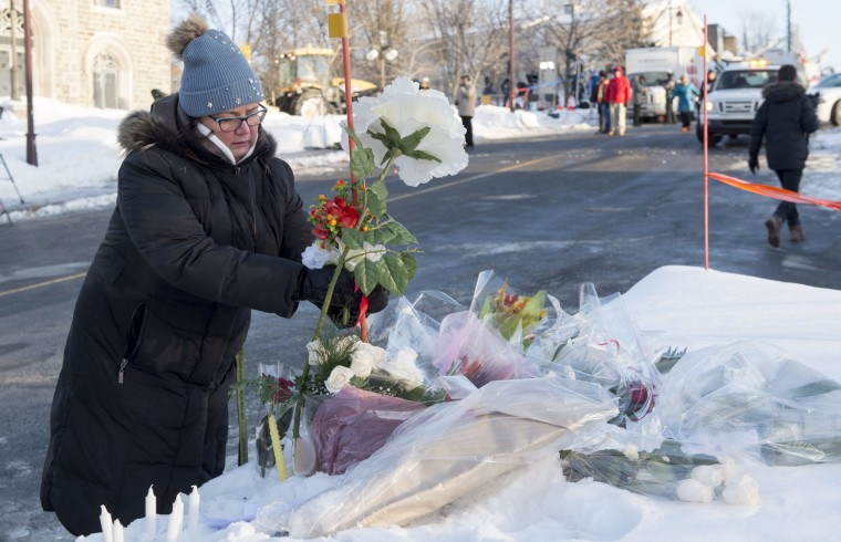 A woman places flowers for victims of a shooting Sunday at a mosque in Quebec City at Dalhousie University in Halifax on Monday, Jan. 30, 2017. Multiple people died in the attack which occurred during evening prayers. (Andrew Vaughan/The Canadian Press via AP)