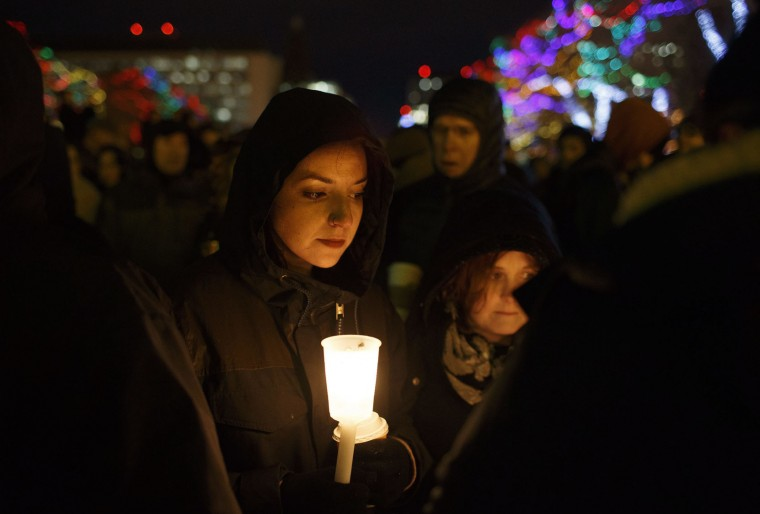 A woman joins others as they gather in remembrance of the victims of Sunday's shooting at a Quebec City mosque, during a vigil in Edmonton, Alberta, Monday, Jan. 30, 2017. A French Canadian known for far-right, nationalist views was charged Monday with six counts of first-degree murder and five counts of attempted murder over the shooting rampage at a Quebec City mosque that Canada's prime minister called an act of terrorism against Muslims. (Jason Franson/The Canadian Press via AP)