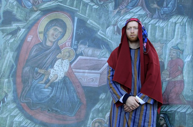 A Georgian man stands by a mural as he waits to participate in a religious procession to mark Orthodox Christmas in Tbilisi, Georgia, Saturday, Jan. 7, 2017. Christmas falls on Jan. 7 for Orthodox Christians that use the old Julian calendar instead of the 16th-century Gregorian calendar adopted by Catholics and Protestants and commonly used in secular life around the world. (AP Photo/Shakh Aivazov)