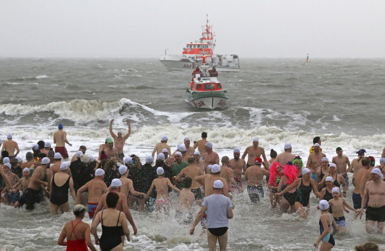 Courageous participants run into the four degree Celsius (39 F) cold North Sea during a New Year's swim on the island of Norderney, Germany, Sunday, Jan. 1, 2017. (Sabine Sykora/dpa via AP)
