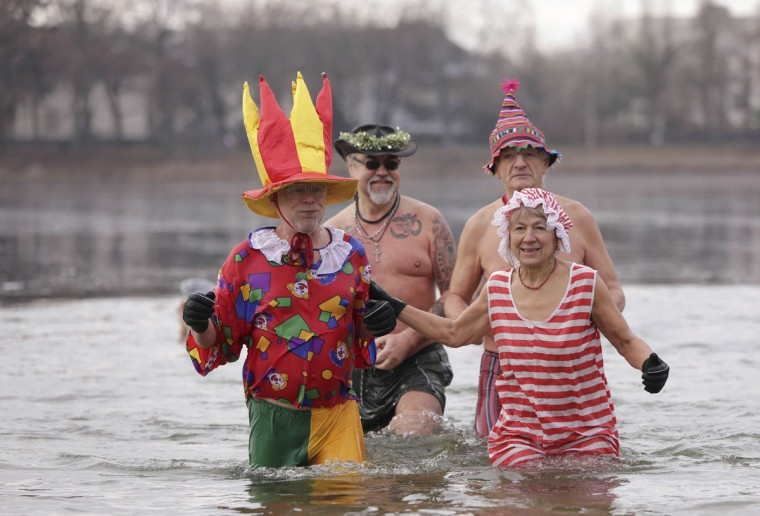 Winter swimmers from the 'Berliner Seehunde' club go for a New Year's swim in lake Orankesee at temperatures around 1 degree Celsius (33,8 F) in Berlin, Germany, Sunday, Jan. 1, 2017. (Joerg Carstensen/dpa via AP)