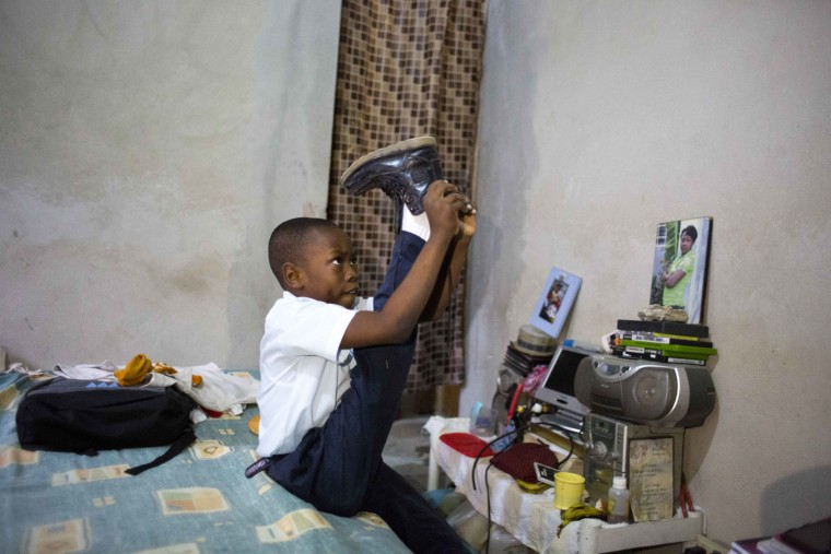 In this Jan. 10, 2017 photo, Judeley Hans Debel pulls a shoe on his prosthetic leg as he gets ready for school at home in Petion-Ville, Haiti. Seven years after his mother dug his 2 ½ year body out of the earthquake rubble, Judeley refuses to let his disability hold him back. (AP Photo/Dieu Nalio Chery)