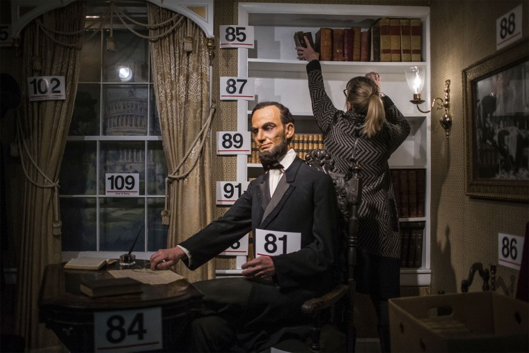 A wax figure of President Abraham Lincoln is displayed in the foreground as Karen Foust removes books she purchased during the Hall of Presidents and First Ladies Museum auction in Gettysburg, Pa., Saturday, Jan. 14, 2017. The museum, which displayed the figures of 44 presidents and their first ladies, operated on Baltimore Street for 60 years, the company said in a news release. (Sean Simmers /PennLive.com via AP)
