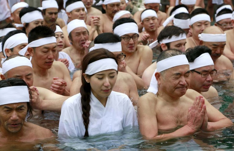 Japanese bathers pray for the healthy new year while dipping in a cold water tub with blocks of ice at a park by Teppozu Inari Shinto Shrine during a winter ritual in Tokyo, Sunday, Jan. 8, 2017. About 100 people gathered for the mid-winter event to pray for their healthy new year and displayed their perseverance. (AP Photo/Shizuo Kambayashi)