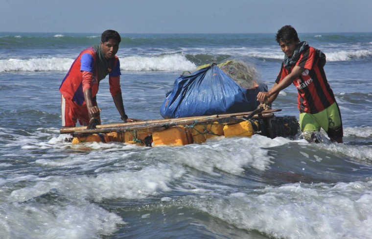 In this Jan. 16, 2017, photo, Rohingya fishermen pull their raft made of empty plastic containers along the coastline of the Bay of Bengal in Tha Pyay Taw village, Maungdaw, western Rakhine state, Myanmar. Their usual, sturdy fishing boats were outlawed three months ago when Myanmar authorities launched a sweeping and violent counter-insurgency campaign in Rakhine state, home to the long-persecuted Rohingya Muslim minority. The ban on fishing boats -- meant to prevent insurgents from entering or leaving the country by sea -- is just one small provision in the wider crackdown, in which authorities have been accused of widespread abuses. (AP Photo/Esther Htusan)