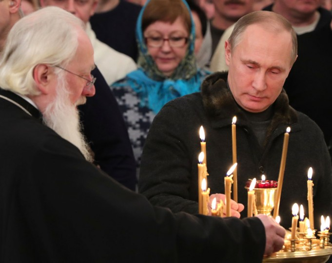 Russian President Vladimir Putin, right, lights a candle prior to a midnight Orthodox Christmas Mass at the St. George's Monastery, Novgorod Region, about 500 kilometers (300 miles) northwest of Moscow, Russia, Friday, Jan. 6, 2017. Orthodox Christians celebrate Christmas on Jan. 7, in accordance with the Julian calendar. (Mikhail Klimentyev, Sputnik, Kremlin Pool Photo via AP)