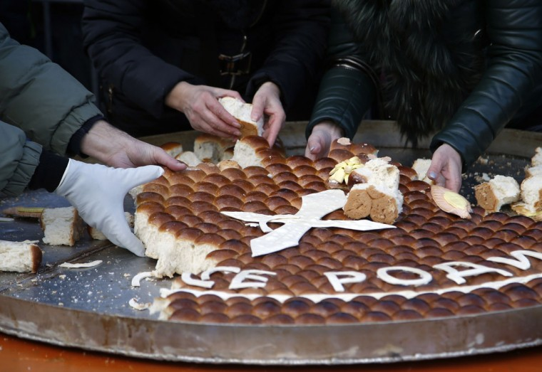 People break traditional Christmas bread to mark the Orthodox Christmas Day festivities in Belgrade, Serbia, Saturday, Jan. 7, 2017. Children traditionally scramble for a piece of the bread, searching for a gold coin, hidden inside. (AP Photo/Darko Vojinovic)