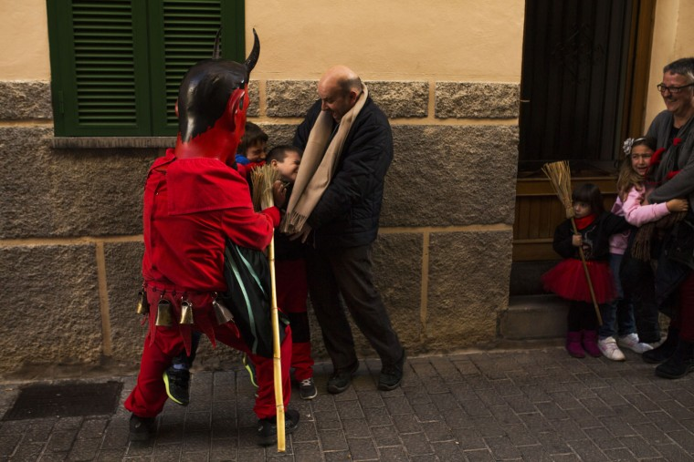 In this photo taken on Monday, Jan. 16, 2017, a reveler dressed as a demon called 'Dimonis' scares children with a broom during traditional celebrations in honor of Saint Anthony in Sa Pobla village at the Mediterranean island of Mallorca, Spain. Mixing pagan and religious traditions from medieval times, the fire and demon festivals are held in towns across the island of Mallorca each Jan. 16-17 to celebrate the day of Saint Anthony the Abbot, the patron saint of animals. (AP Photo/Francisco Seco)