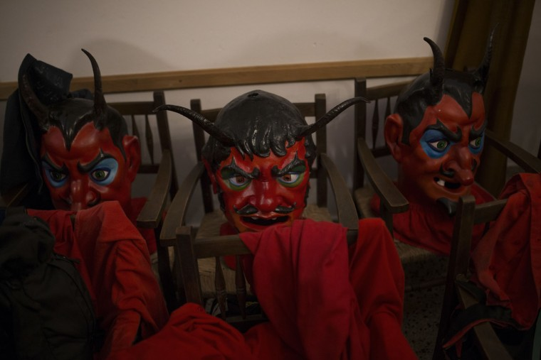 In this photo taken on Monday, Jan. 16, 2017, 'dimonis' or demon masks and costumes lay on chairs before being used by revelers during traditional celebrations in honor of Saint Anthony in Sa Pobla village at the Mediterranean island of Mallorca, Spain. Mixing pagan and religious traditions from medieval times, the fire and demon festivals are held in towns across the island of Mallorca each Jan. 16-17 to celebrate the day of Saint Anthony the Abbot, the patron saint of animals. (AP Photo/Francisco Seco)