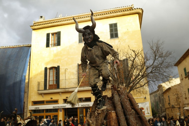 In this photo taken on Monday, Jan. 16, 2017, a reveler dressed as a demon called 'Dimonis' jumps from atop a pile of wood during traditional celebrations in honor of Saint Anthony in Alcudia village at the Mediterranean island of Mallorca, Spain. Mixing pagan and religious traditions from medieval times, the fire and demon festivals are held in towns across the island of Mallorca each Jan. 16-17 to celebrate the day of Saint Anthony the Abbot, the patron saint of animals. (AP Photo/Francisco Seco)