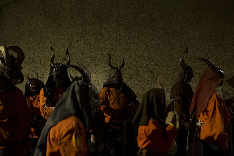 In this photo taken on Monday, Jan. 16, 2017, revelers dressed as demons called 'Dimonis' stand before taking part in a 'Correfoc' or 'run with fire' party during traditional celebrations in honor of Saint Anthony in Muro village in the Mediterranean island of Mallorca, Spain. Mixing pagan and religious traditions from medieval times, the fire and demon festivals are held in towns across the island of Mallorca each Jan. 16-17 to celebrate the day of Saint Anthony the Abbot, the patron saint of animals. (AP Photo/Francisco Seco)
