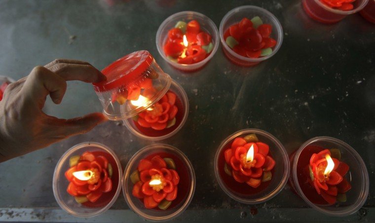 Ethnic Chinese Thais light candles after praying at the Leng Nuei Yee Chinese temple in Bangkok, Thailand, Tuesday, Jan. 24, 2017. Chinese New Year falls on Jan. 28, this year, marking the start of the Year of Rooster according to the Chinese lunar calendar. (AP Photo/Sakchai Lalit)