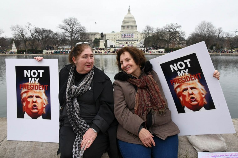 "Elaine Sarao, 66, left, from the DC area, and Beverly Friedman, 72, of Brooklyn, NY, sit by the reflecting pool across from the Capitol. Sarao said, ""Mr. Trump is illegitimate, and is a danger to America and the world."" (Amy Davis/Baltimore Sun)"
