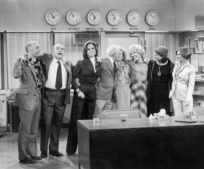 1977: The cast of 'The Mary Tyler Moore Show' stands with their arms around each other in the newsroom in a promotional portrait for the series finale. L-R: Gavin MacLeod, Edward Asner, Mary Tyler Moore, Ted Knight, Betty White, Georgia Engel, Valerie Harper and Cloris Leachman. (Photo by CBS Photo Archive/Getty Images)