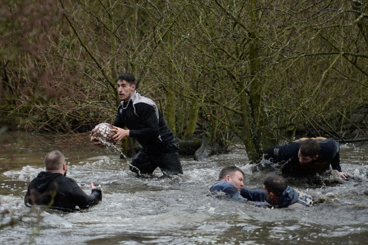 Competitors from the opposing teams, the Up'ards and the Down'ards, vie for the ball during the annual Royal Shrovetide Football Match in Ashbourne, northern England, on February 28, 2017. The mass-participation ball game involves two teams, whose players are defined by which side of a small brook that bisects the town they were born, aiming to score a goal, which are some three miles apart. The game, which has very few rules, is played over two 8 hour periods on Shrove Tuesday and Ash Wednesday. Royal Shrovetide Football is believed to have been played annually in Ashbourne since 1667. (AFP PHOTO / Oli SCARFF)