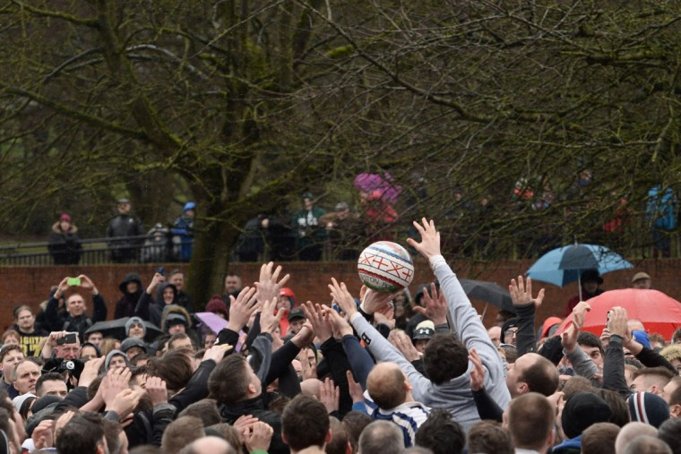The ball is caught at the start of the annual Royal Shrovetide Football Match in Ashbourne, Derbyshire, England on February 28, 2017 between the two opposing team's, the Up'ards and the Down'ards. The mass-participation ball game involves two teams, whose players are defined by which side of a small brook that bisects the town they were born, aiming to score a goal, which are some three miles apart. The game, which has very few rules, is played over two 8 hour periods on Shrove Tuesday and Ash Wednesday. Royal Shrovetide Football is believed to have been played annually in Ashbourne since 1667. (AFP PHOTO / Oli SCARFF)