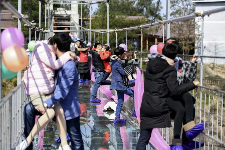 Chinese couples kiss as they stand on a glass bridge during a kissing contest on Valentine's Day in Pingjiang, central China's Hunan province on February 14, 2017. (AFP/Getty Images)