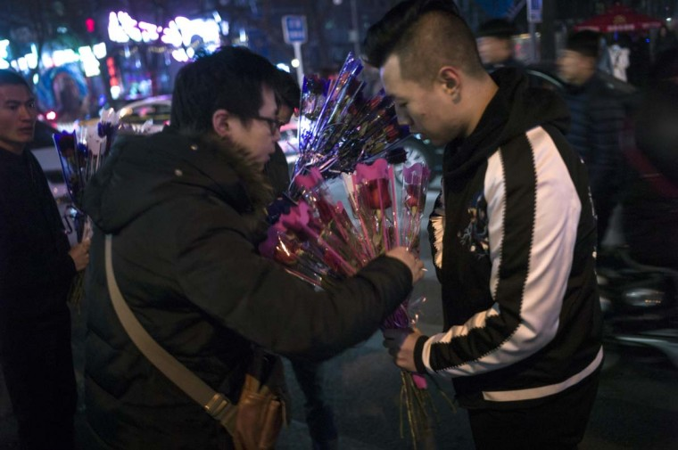 Pedestrians buy flowers from a vendor during Valentine's Day on a street in Beijing on February 14, 2017. A Pakistani court has banned public celebrations of Valentine's Day in the capital Islamabad while Indonesian students plan to spurn the event, as the festival of love gets a chilly reception in parts of Asia. (FRED DUFOUR/AFP/Getty Images)