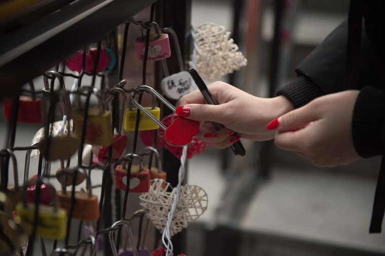 A woman attaches a love lock at a shopping mall on Valentine's Day in Beijing on February 14, 2017. (NICOLAS ASFOURI/AFP/Getty Images)